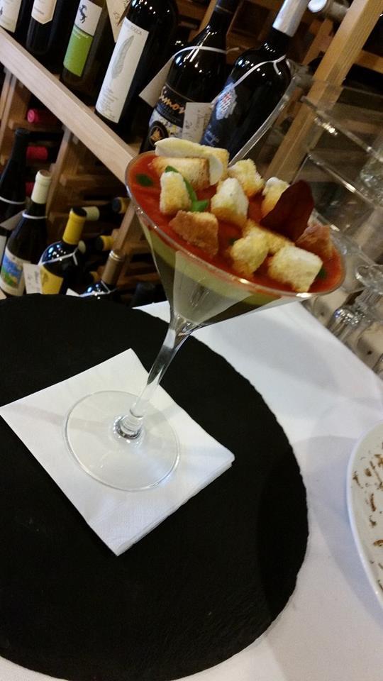 una coppa di vetro con una mousse tricolore con sopra dei crostini appoggiata su un centrino rotondo nero sopra a un tavolo