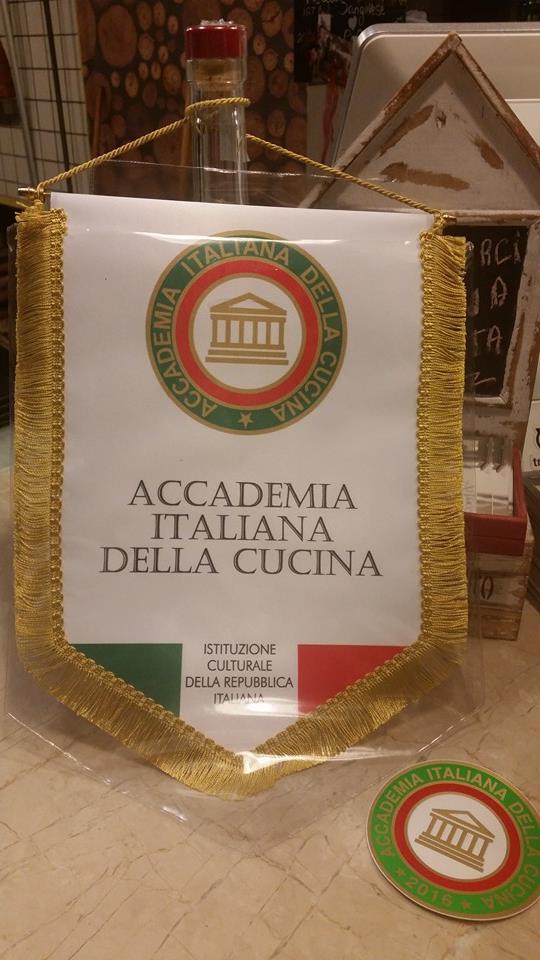 riconoscimento a forma di bandiera appeso a una bottiglia con scritto ACCADEMIA ITALIANA DELLA CUCINA