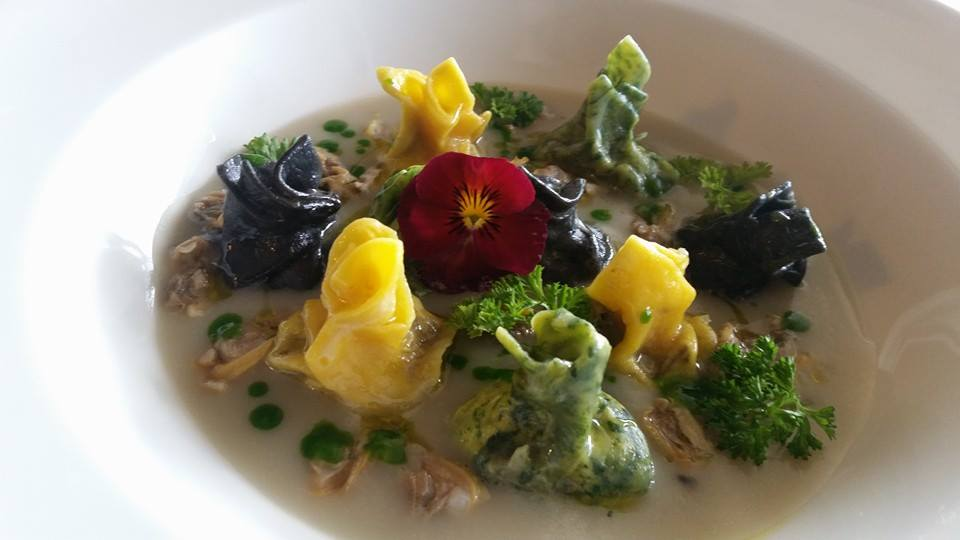 piatto a base di ravioli al nero, di seppia, agli spinaci e classici con fiore al centro del piatto