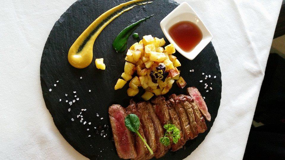 tagliata  di carne al sangue con patate, decorazioni con salse gialle e verdi e accanto un piccolo recipiente con una salsa rossa