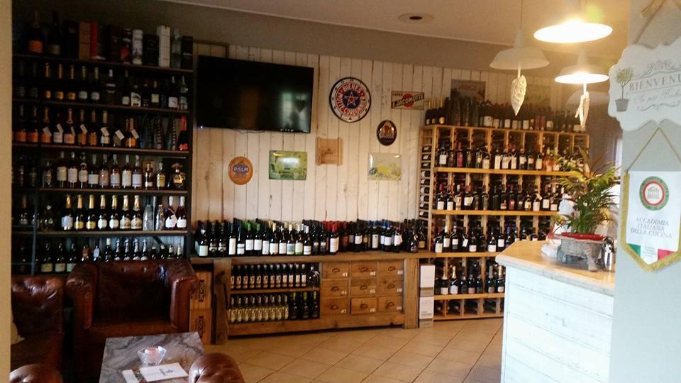 interno del ristorante, angolo enoteca con tanti vini esposti in mobili di legno e sulla sinistra due poltrone bordeaux