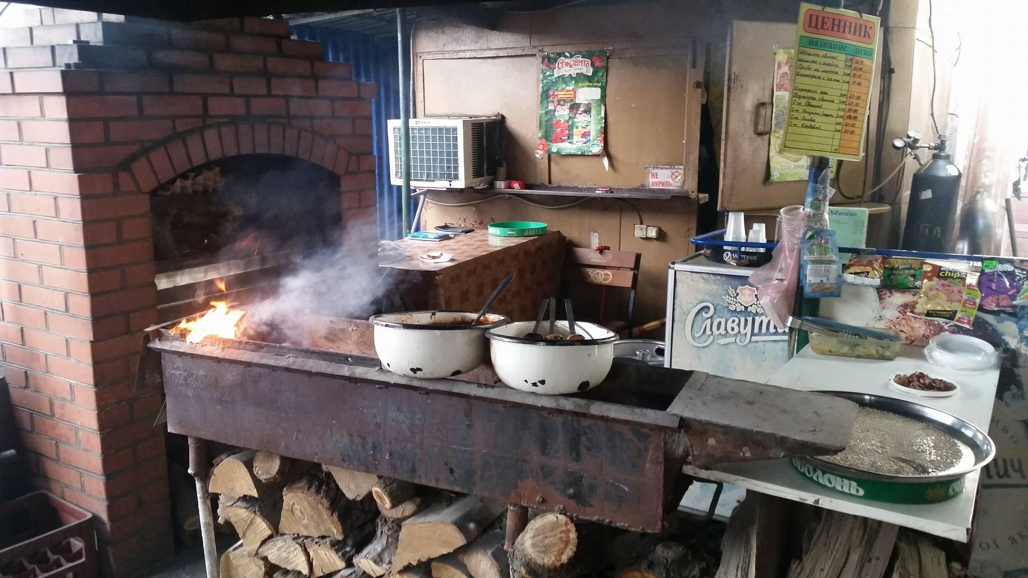 cucina con forno a legna con mattoni a vista, due casseruole bianche su una struttura di ferro con sotto della legna e sulla destra un piano di lavoro con dei vassoi e del cibo