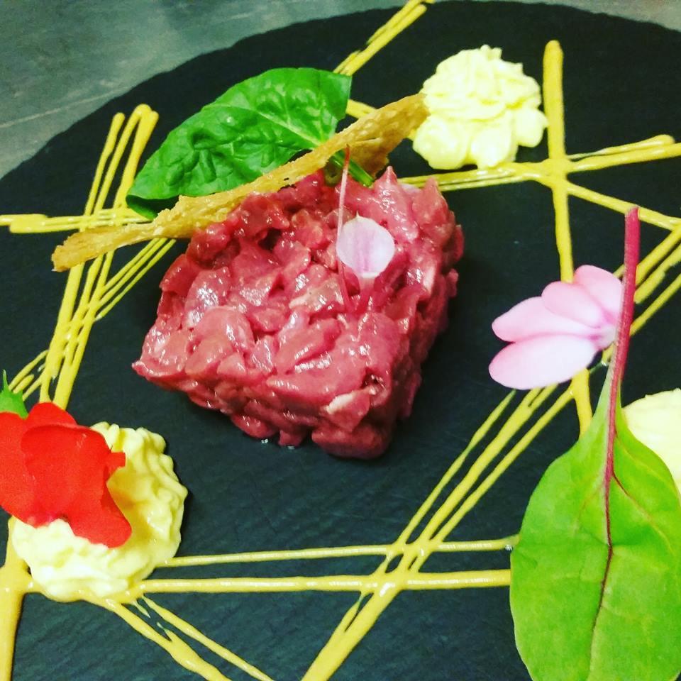 tartare di carne con mousse ai lati del piatto, basilico, petali di fiori rosa e salsa gialla decorativa che forma una specie di reticolato sul piatto
