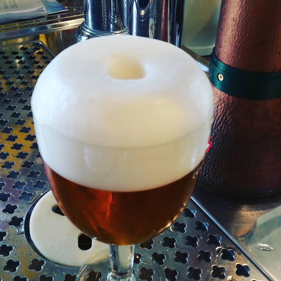 un bicchiere di birra con tanta schiuma visto da vicino