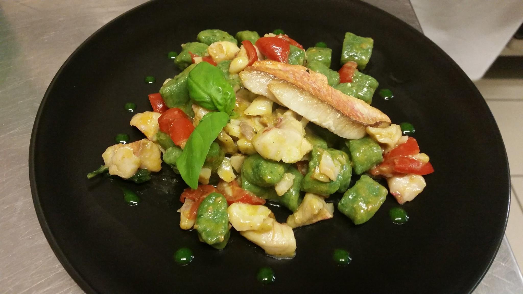 piatto a base di pesce in salsa verde e pomodori tagliati