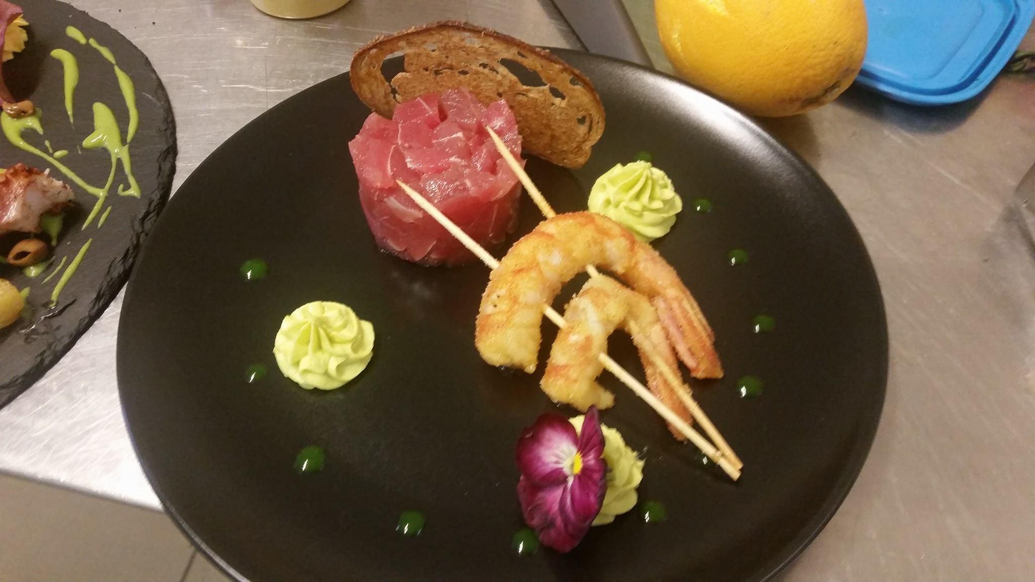 spiedini di gamberi, con tartare di carne, fetta di pane, mousse e fiori nel piatto