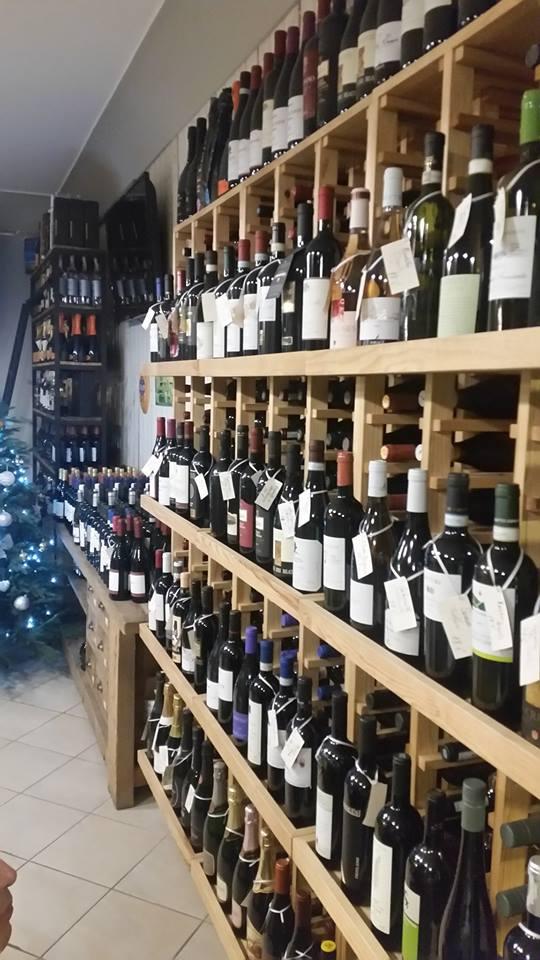 vini esposti negli scaffali di legno nell'angolo enoteca visti lateralmente