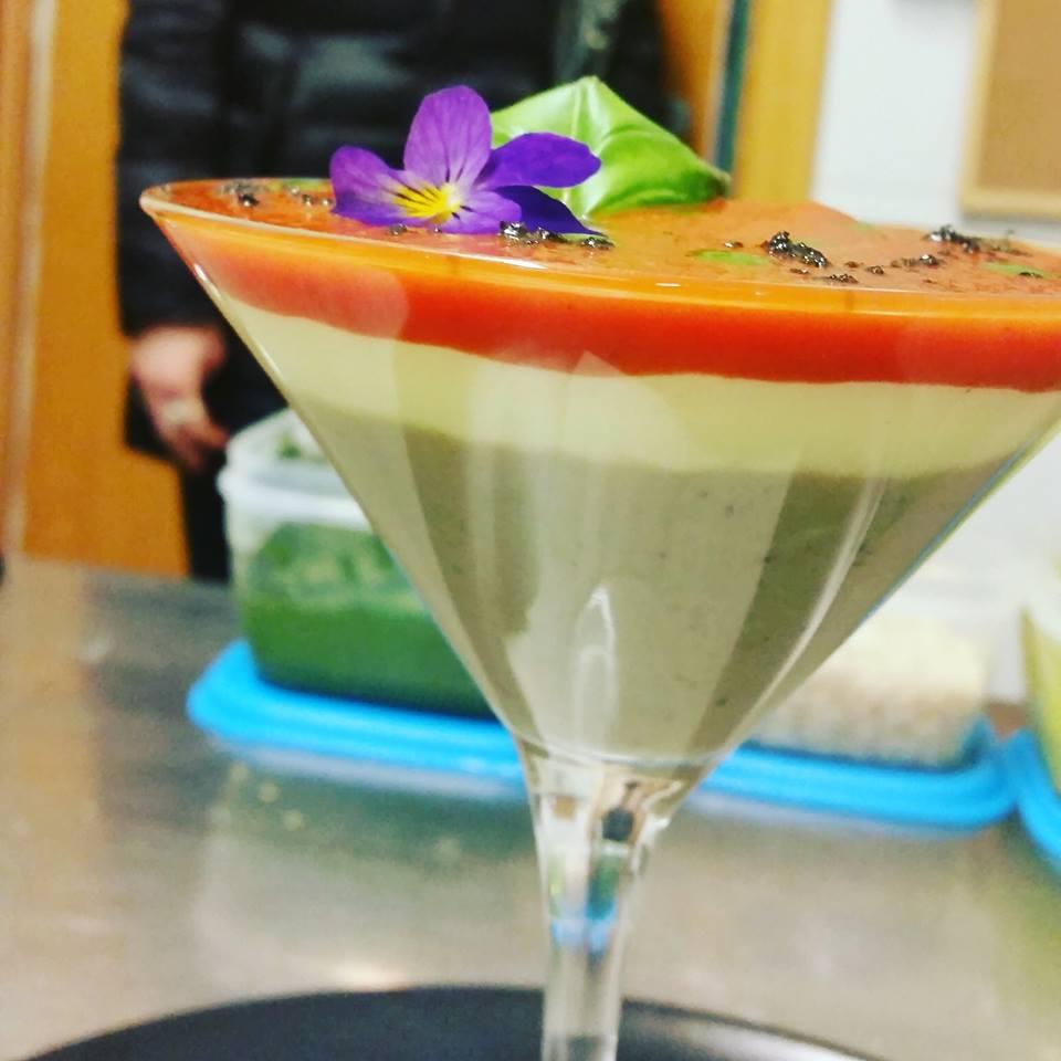 coppa di mousse tricolore, arancione, crema,beige e in cima basilico e petalo di violetta