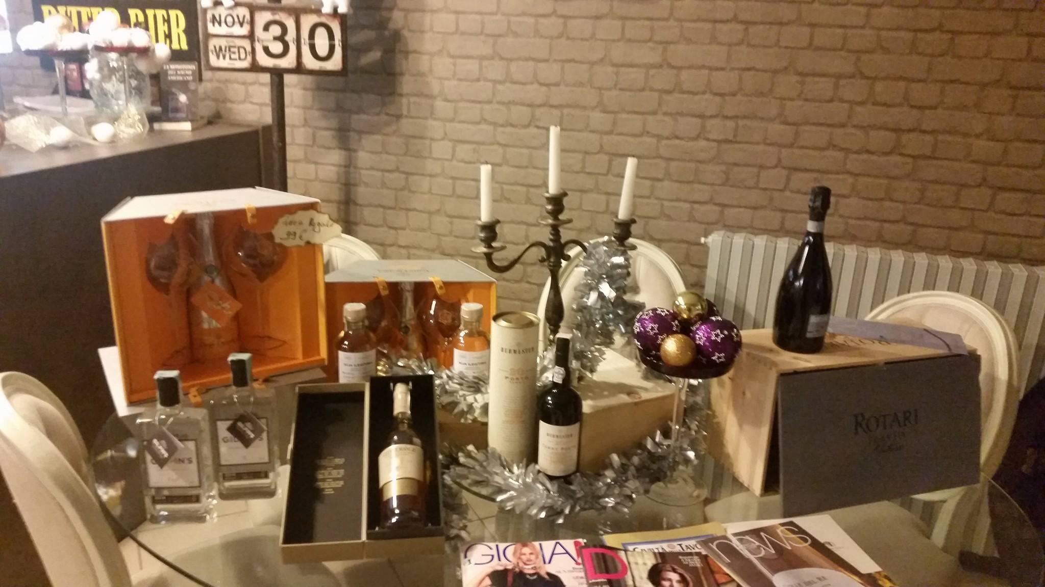 tavola con riviste,candelabro e serie di liquori esposti con le loro scatole