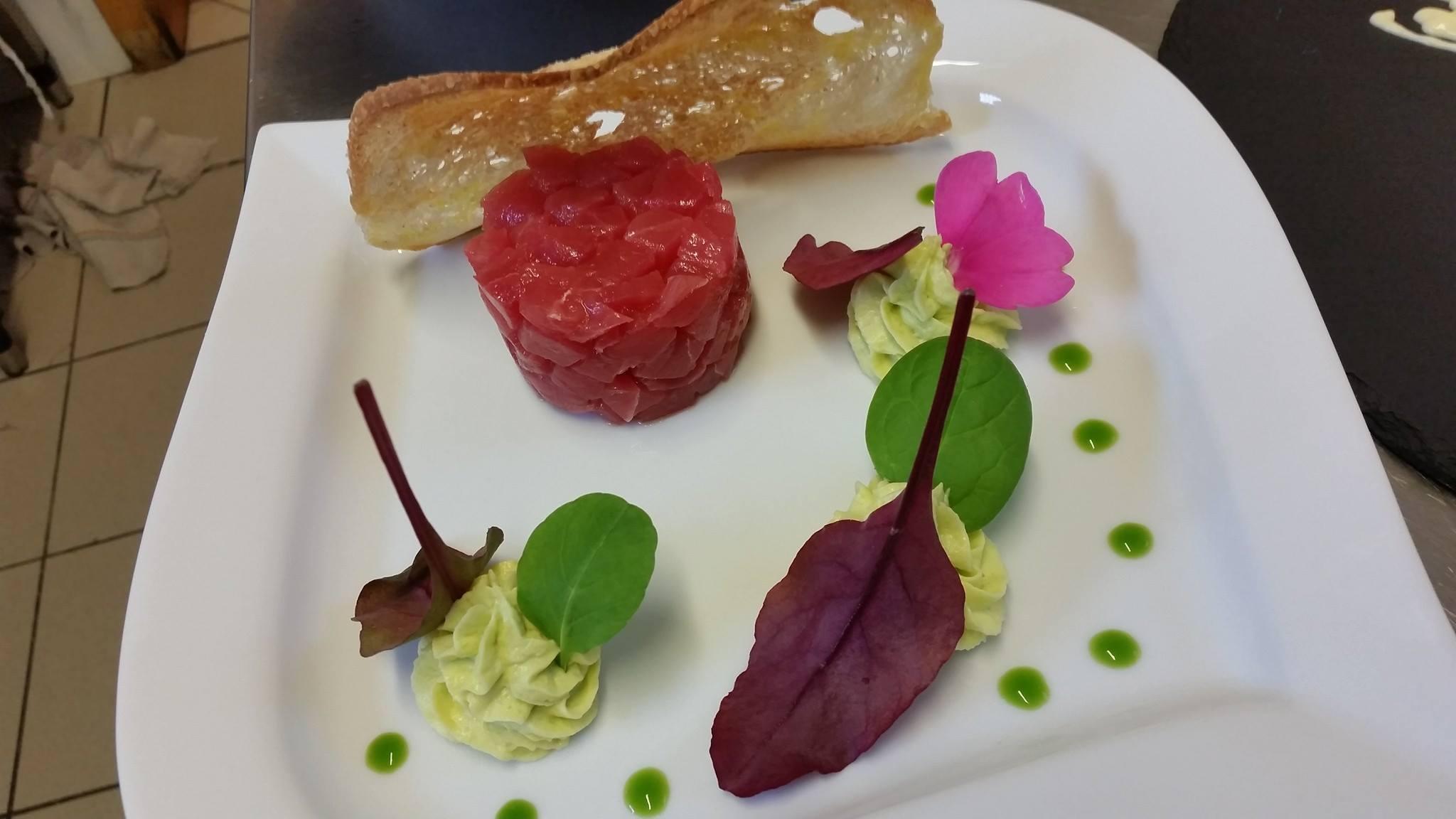 tartare di carne, mousse, fetta di pane, basilico, salsa verde decorativa, foglie e petali di fiore rosa