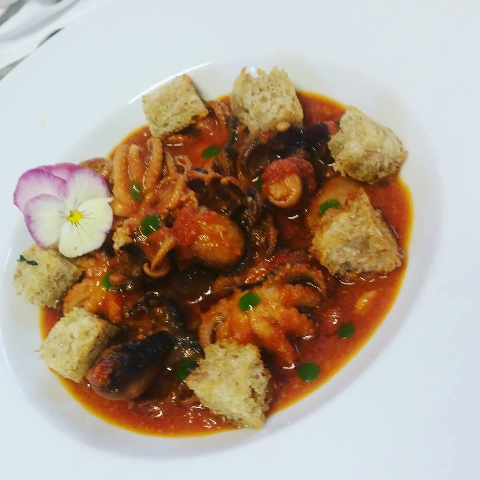 piatto con polipi in salsa al pomodoro con salsa verde, crostini e violetta