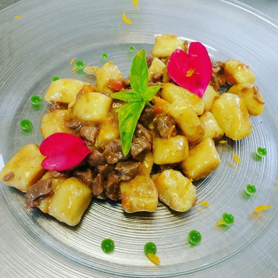 piatto di patate e carne con salsa verde e petali rosa a forma di cuore, il tutto su un piatto di cristallo
