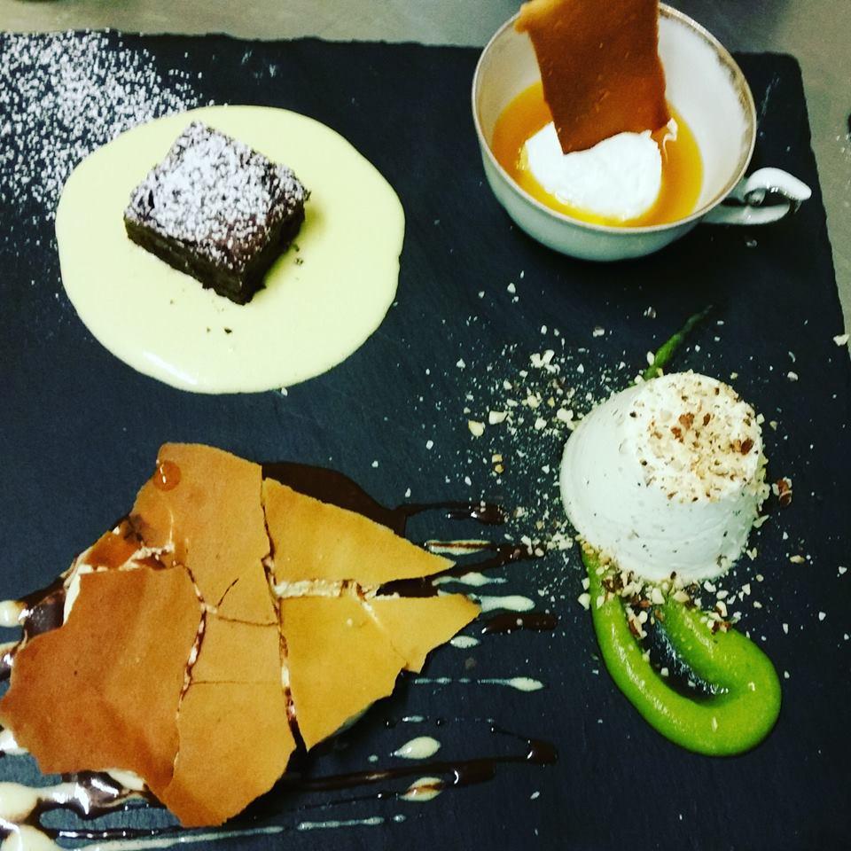 serie di dolci, brownie con zucchero a velo, panna cotta con praline, salsa verde decorativa e altre specialita'