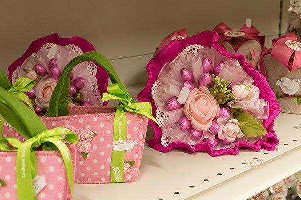 delle borsette rosa a pois bianchi e delle composizioni di fiori con ovetti di Pasqua