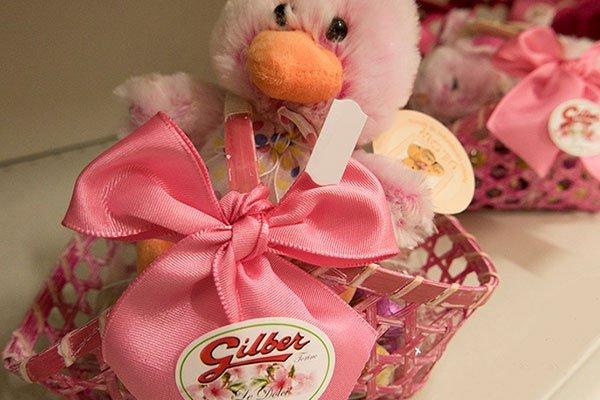 un cesto rosa con scritto Gilber e un peluche di un papero