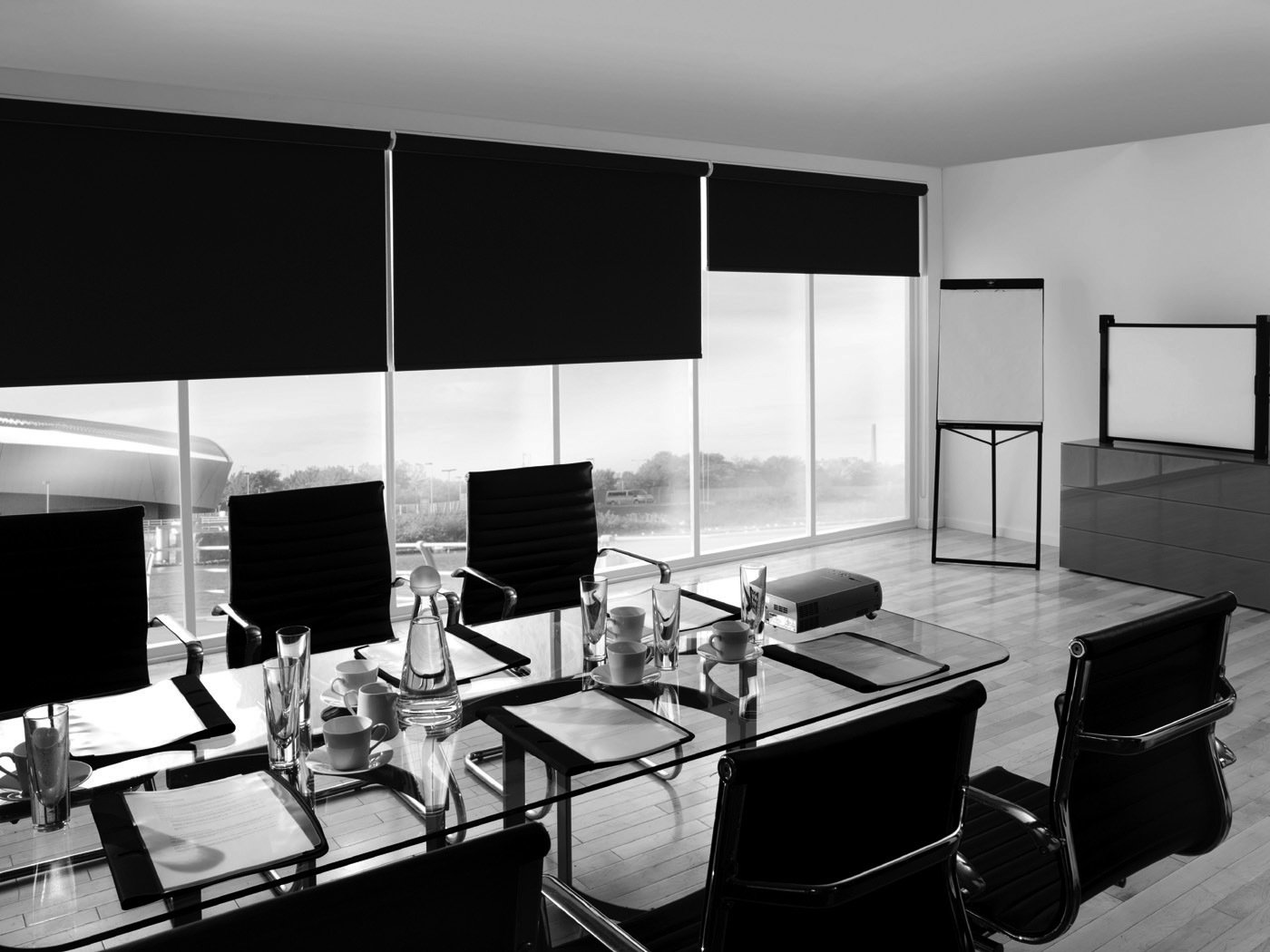 A office with long black blinds over the windows