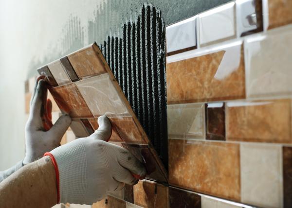 mani di un operaio con guanti mentre fissa piastrelle a parete