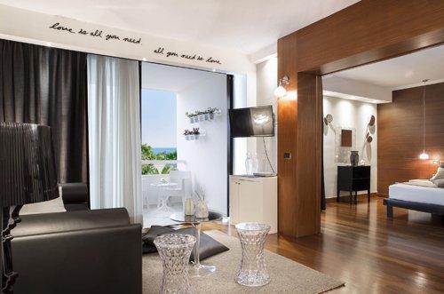 camera matrimoniale con divano nero e balcone presso presso l'Hotel Mec Paestum a Capaccio