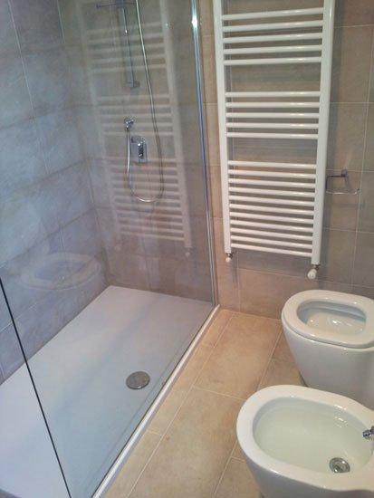 il vetro di un box doccia, un wc e un bidet