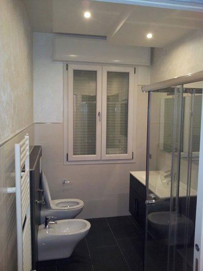 un bagno con sulla sinistra wc e bidet e sulla destra lavabo e box doccia