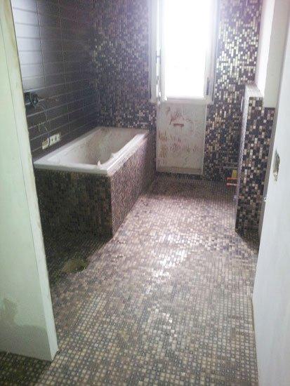 un bagno con pavimento e muri con piastrelle a mosaico e vista di una vasca