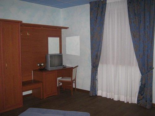 un armadio in legno e una scrivania con sopra una Tv