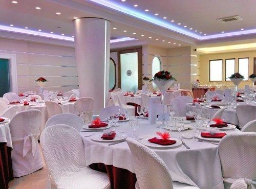 dei tavoli apparecchiati  decorati con dei fiori rossi
