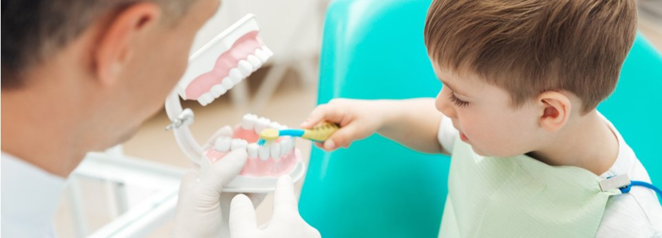 dentista spiega a un bambino come si lavano i denti
