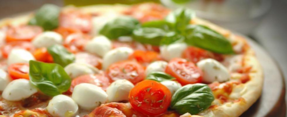 primo piano di una pizza con mozzarelline pomodorini e basilico