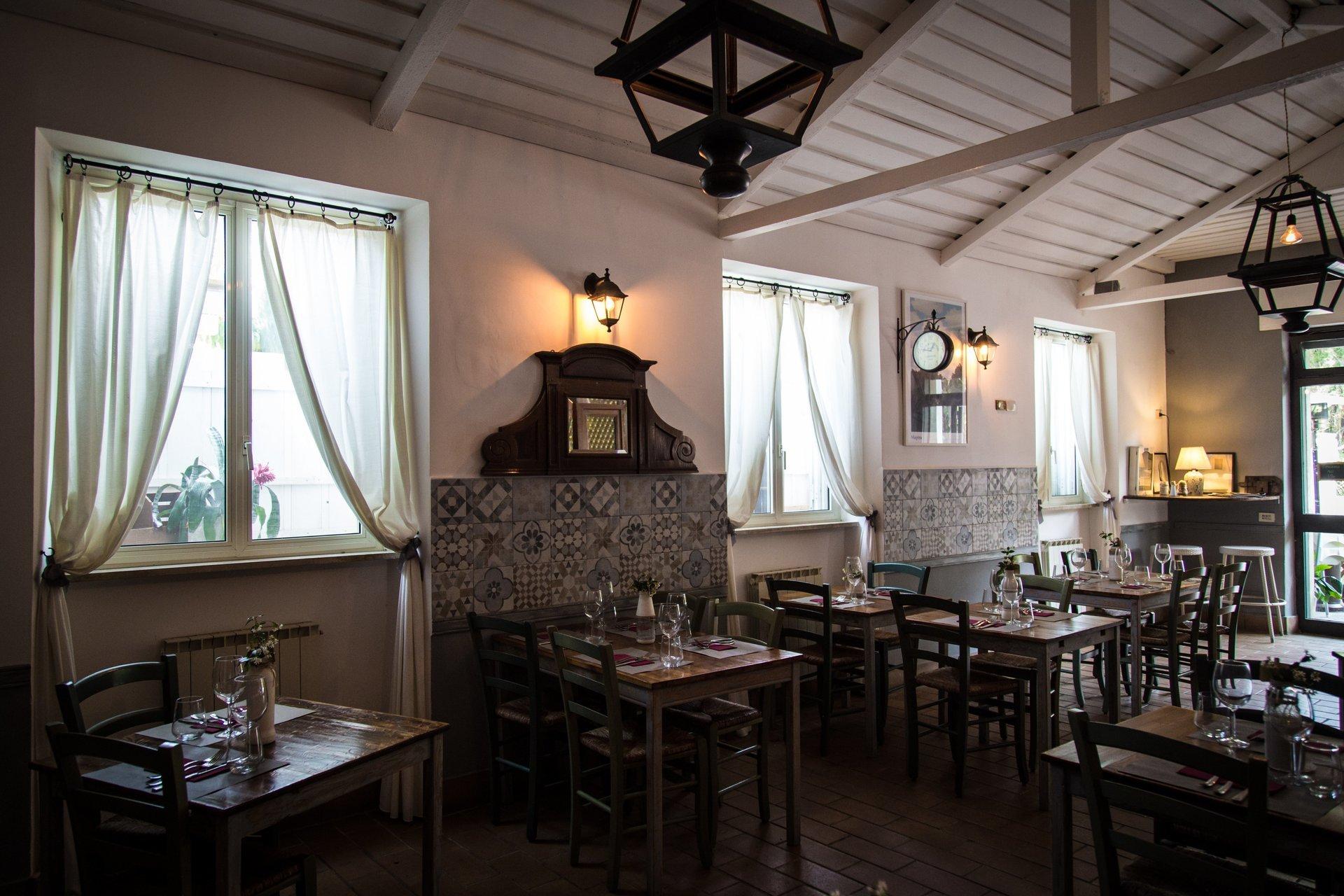 tavoli in legno apparecchiati dentro il ristorante