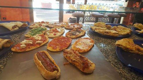 un tavolo con delle pizze, hot dog e altre specialità