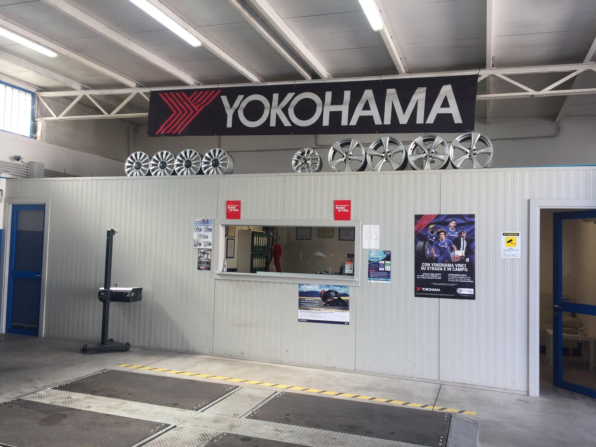 vista dell'ufficio all'interno dell'officina e uno striscione con scritto Yokohama