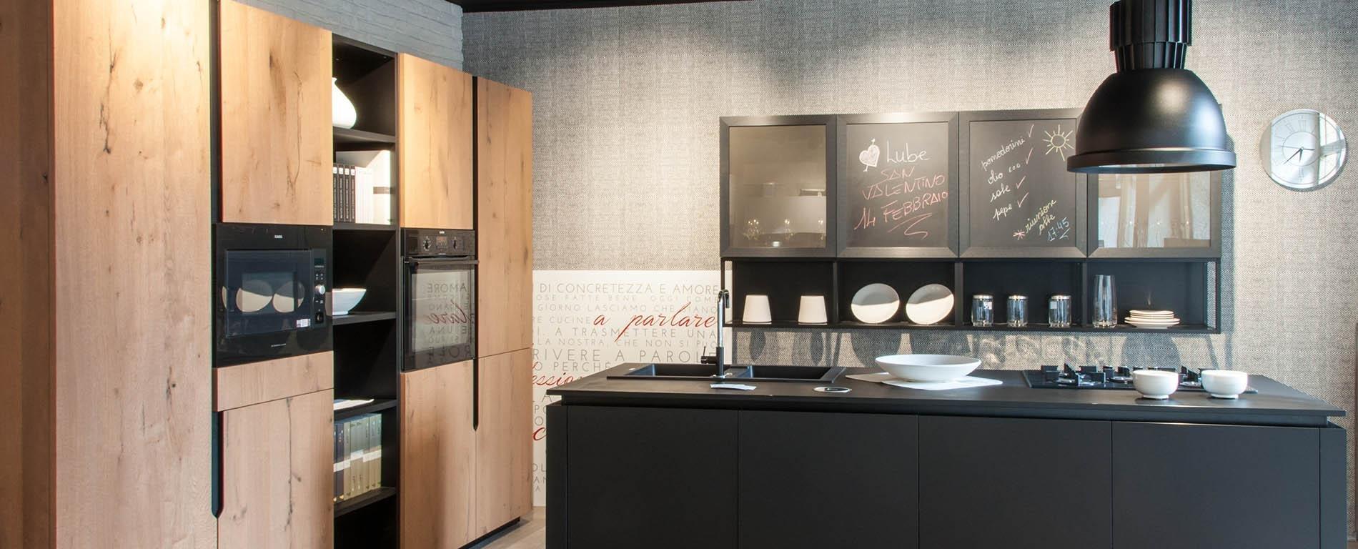 una cucina con mobili neri e in legno