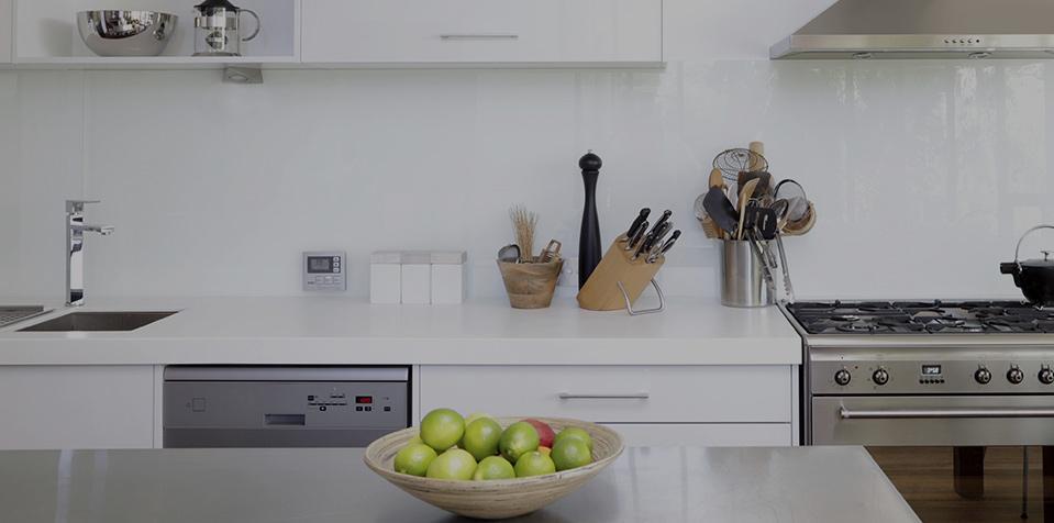 una cucina con top bianco e un tavolo con un cestino di limoni