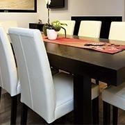 un tavolo nero con sedie bianche