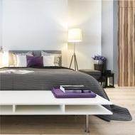 un letto con un lenzuolo grigio e un comodino con una lampada