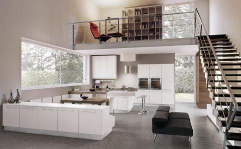 cucina con mobili di color bianco e vista delle scale che portano al piano superiore