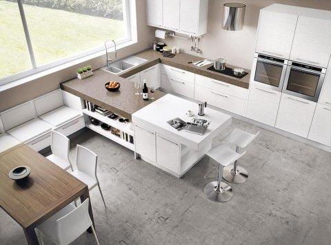 una cucina moderna con mobili bianchi, un tavolo con le sedie e sopra un lampadario