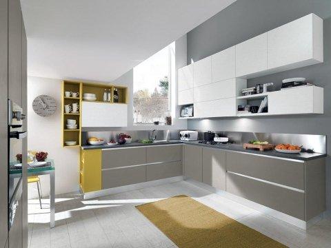 una cucina angolare con mobili gialli ,grigi e bianchi