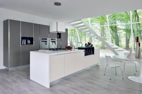 una cucina con mobili grigi, una penisola bianca e vista delle scale