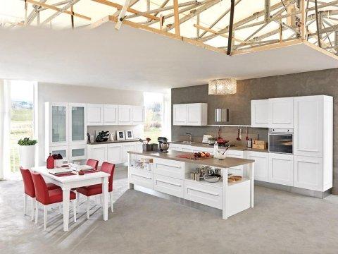 cucina moderna con mobili bianchi e un tavolo con sedie rosse