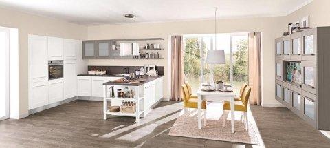 cucina bianca e  marrone e un tavolo con sedie gialle