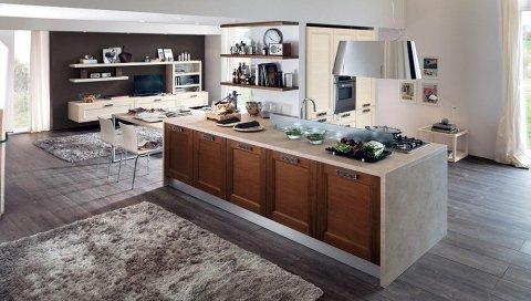 una penisola di una cucina con mobili in legno e top color beige