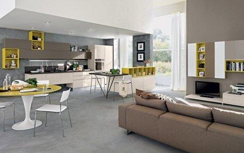 un salotto con un divano marrone e una cucina con mobili gialli e beige