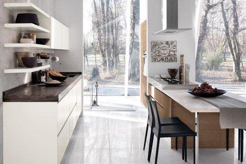 una cucina con mobili bianchi e marroni e delle sere nere