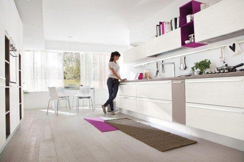 una donna con le mani appoggiate sui mobili di una cucina di color bianco e beige