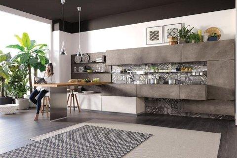 donna seduta su uno sgabello in una cucina moderna con mobili marroni
