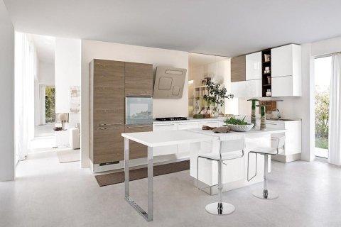 in cucina con mobili marroni e bianche e un tavolo con due sedie