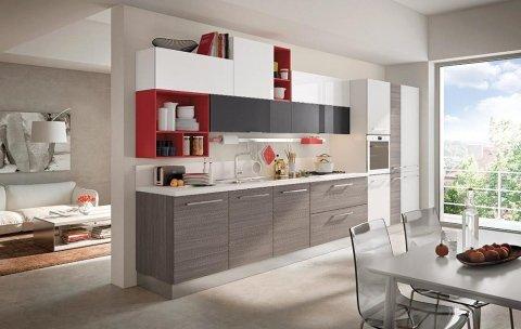 una cucina a blocco con mobili marroni, bianchi, neri rossi