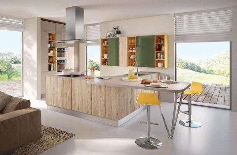 una cucina angolare con una cappa in acciaio e due sedie gialle
